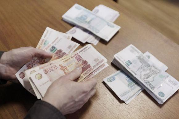 An employee of a local company, producing equipment for electrical meters, counts Russian rouble banknotes in Stavropol